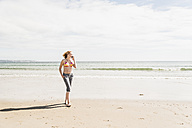 Teenage girl on cell phone walking on the beach - UUF08399