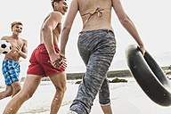 Friends running with a ball and tyre on the beach - UUF08423
