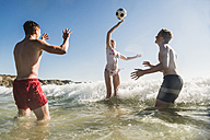 Friends playing with a ball in the sea - UUF08426