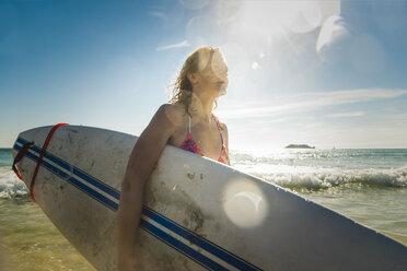 Teenage girl carrying surfboard at the sea - UUF08438