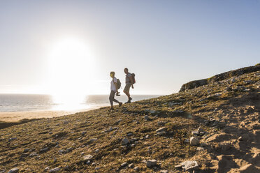 France, Bretagne, Finistere, Crozon peninsula, couple during beach hiking - UUF08459