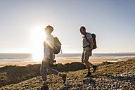 France, Bretagne, Finistere, Crozon peninsula, couple during beach hiking - UUF08462