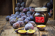 Preserving jar of homemade plum jam and plums on wood - LVF05290