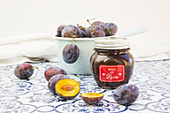 Preserving jar of homemade plum jam and plums on tiles - LVF05299