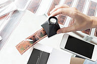 Woman checking film strips with magnifying glass - KNTF00484