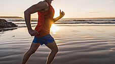 France, Crozon peninsula, jogger on the beach at sunset - UUF08487
