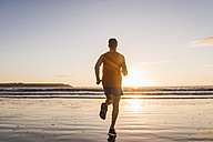 France, Crozon peninsula, jogger on the beach at sunset - UUF08490