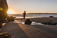 France, Crozon peninsula, jogger on the beach at sunset - UUF08493
