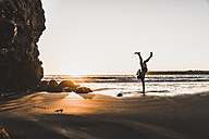 France, crozon peninsula, young man doing handstand on one arm at sunset - UUF08499