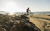 France, Crozon peninsula, Man biking on the beach - UUF08502