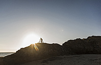 France, Crozon peninsula, mountainbiker at sunset - UUF08508
