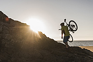 France, crozon peninsula, mountainbiker carrying his bike at sunset - UUF08511