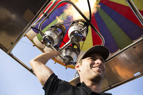 Man using burners of a hot air balloon - ABZF01233