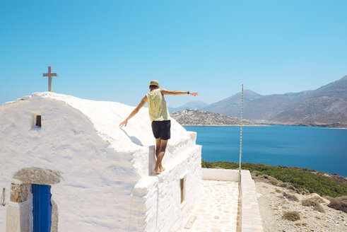 Greece, Nikouria, back view of tourist balancing on spur of small church - GEMF01012
