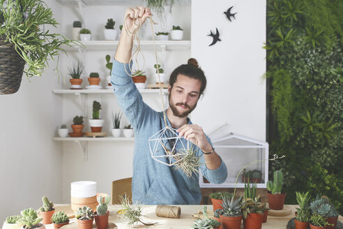 Plant collector preparing the pendant for an air plant - RTBF00359
