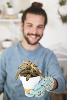 Young man holding succulent plant - RTBF00371