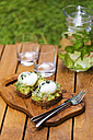 Slices of toast with mashed avocado, boiled egg and sprouts - KNTF00494