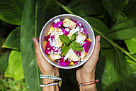 Woman's hands holding bowl of tropical fruit salad - KNTF00503