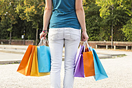 Back view of young woman with colorful shopping bags - SARF02868
