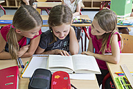 Three schoolgirls reading a book - SARF02890
