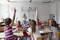 Active pupils raising their hands in class - SARF02896