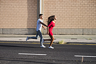 Teenage couple running hand in hand on a street - SIPF00842