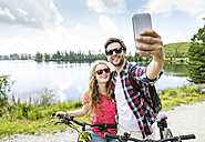 Young couple taking selfies on a bicycle trip - HAPF00856