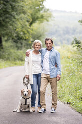 Portrait of happy senior couple with dog in nature - HAPF00871