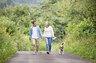 Happy senior couple on a walk with dog in nature - HAPF00877