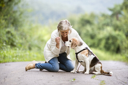 Senior woman with her dog in nature - HAPF00886