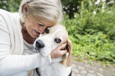 Happy senior woman cuddling her dog - HAPF00889