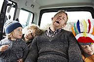 Sleeping father sitting in car on back seat with his sons - FSF00453