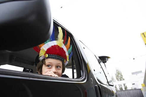 Boy with feather headdress looking out of car window - FSF00456