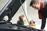 father looking at broken car, while children are waiting - FSF00486