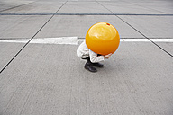 Little girl crouching in street, hiding under orange sphere - FSF00489