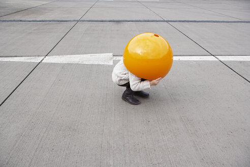 Little girl crouching in street, hiding under orange sphere - FSF00489
