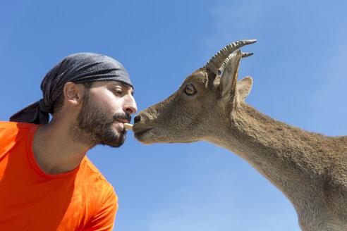 Man feeding Western Spanish ibex - ERLF00189