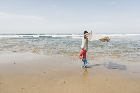 Mature woman walking on the beach lifting a blanket - UUF08564