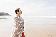 Mature woman wrapped in a blanket on the beach - UUF08570