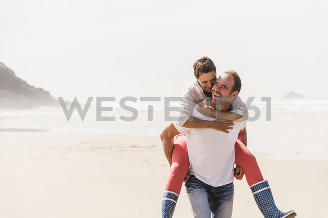 Happy mature man carrying wife piggyback on the beach - UUF08573 - Uwe Umstätter/Westend61