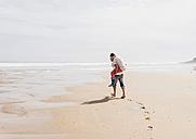 Mature man carrying wife piggyback on the beach - UUF08576