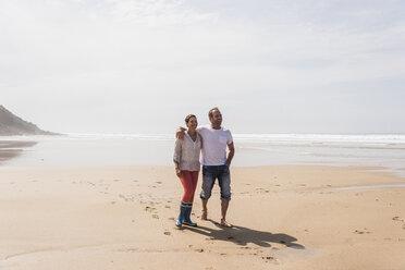 Mature couple walking on the beach - UUF08579