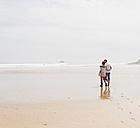 Mature couple walking on the beach - UUF08582