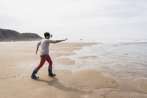 Mature woman on the beach wearing VR glasses - UUF08585