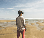 Mature woman standing on the beach wearing VR glasses - UUF08588