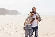 Mature couple walking on the beach - UUF08591