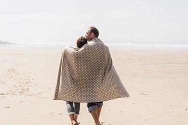 Mature couple walking on the beach - UUF08594