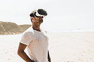 Mature man standing on the beach wearing VR glasses - UUF08597
