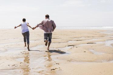 Mature couple running on the beach - UUF08600