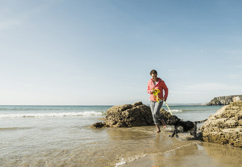 Mature woman walking with dog at the sea - UUF08606